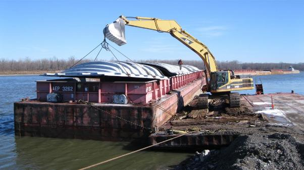 A backhoe places a cover on a barge near Cape Girardeau, Mo. The backhoe had just finished removing fertilizer that was shipped up the river from New Orleans. (Photo by Jacob McCleland for Harvest Public Media)