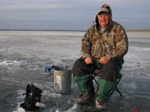 Steve Snyder of Republican City, Neb. fishes for crappie through the lake ice. Snyder said the low water helps fishing in the short term, but threatens the health of the lake. (photo by Grant Gerlock, NET News)