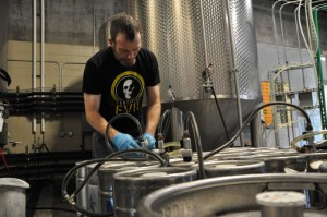Adam Cunningham works on transferring Certified Evil into kegs. The beer is a strong ale crafted by Lucky Bucket Brewing Company in La Vista, Neb. (photo by Ryan Robertson, NET News)
