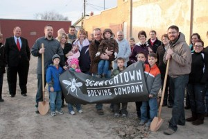 The founders of Scratchtown Brewing Company, along with their families and friends, stand at the future site of the brewery in Ord, Neb. The name of the brewery is an homage to the town's early days, when a wet spring led to an outbreak of insects. (photo by Ryan Robertson, NET News)