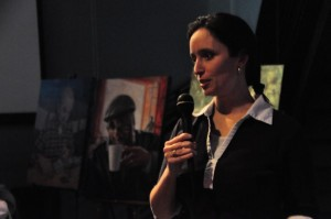Rachel Mindrup, an Omaha based artist, addresses the crowd at a Science Cafe event at the Slowdown Bar in Omaha. Mindrup is the artist behind The Many Faces of NF portrait series. (photo by Ryan Robertson, NET News)