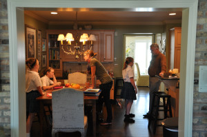 The Paulitz family and Bridgette Paulsen, their nanny, gather in the kitchen as the youngest girls begin homework. (Photo by Ryan Robertson, NET News)