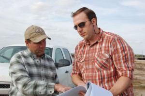 Farmer Mike Hoehne talks with contractor Thad Kuntz about a water storage pit on land Hoehne farms near Gering. (Photo Courtesy NET News)