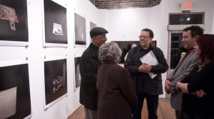Artist Wendel White talks with visitors at his recent exhibit at Carver Bank in north Omaha. The exhibit featured White's photography of objects with historical importance to black Nebraska. (Photo by Hilary Stohs-Krause, NET News)