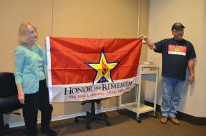 Cliff Leach presents Pat Jameson with a flag in remembrance of her daughter Tricia. (Photo Courtesy UNMC)