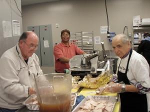 Douglas Thoms (center) helps slice and de-bone turkeys. (Photo Courtesy KVNO News)