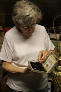 Mary Thompson admires a set of antique spoons. (Photo Courtesy KVNO News)