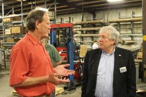 Sid Dindale (right) talks with Craig Pohlman of TSA Manufacturing during a tour of the factory. (Photo by Mike Tobias, NET News)