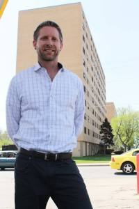 "Christian Gray is the executive director of inCommon Community Development. He stands in front of Park Tower North where the ""You are Here"" mural will be painted. (Photo Courtesy KVNO News)"