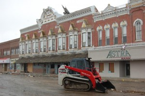 A man in a track loader cleans up downtown Sutton. (Photo by Fred Knapp, NET News)