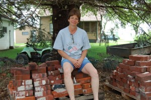 Linda Oertwich with bricks from her bar. (Photo by Fred Knapp, NET News)