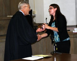 Newcombe (r) accepts a ceremonial coin from Nebraska Chief Justice Mike Heavican. (Photo courtesy Janet Bancroft)