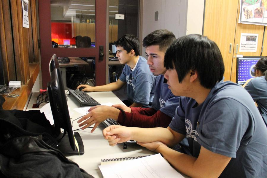 Omaha South students, including Khoa Tran (right) and Miguel Mayorga (center) compete in CyberPatriot. (photo by Mike Tobias, NET News)