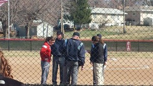 Mav head coach Jeanne Scarpello (in red) huddles with the umps and Fort Wayne coach Germaine Fairchild before Sunday's game. (Courtesy Photo Brandon McDermott)