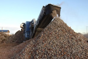 """A large grinder breaks down boulder-sized pieces of concrete and brick into useable gravel. Bob Muhlbach of H.L. Muhlbach Construction said Pilger's debris piles don't constitute the largest job he's worked on, but it is the first time he's had to """"grind up a town."""" (Photo by Ryan Robertson, NET News)"""