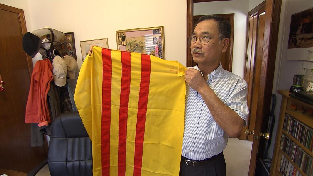 Liem Ha holds a South Vietnamese flag in his Omaha home. (Photo by Tyler Kersting, NET)