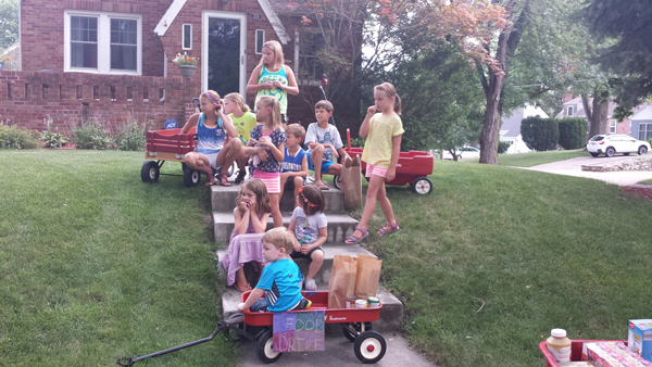 Children from an Omaha community take a break from collecting cans for a neighborhood food drive. The drive was organized as part of 24 Hours of Impact. (photo by Brandon McDermott, KVNO News)
