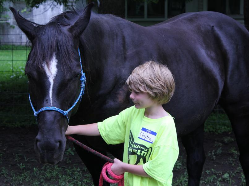 11-year-old Clayton is taking part in equine-assisted or horse-powered learning. He leads Misty the horse to small learning stations strewn across this path. Each one is comprised of physical math problems designed specifically to match Clayton's skill level. (Photo by Ben Bohall, NET News)