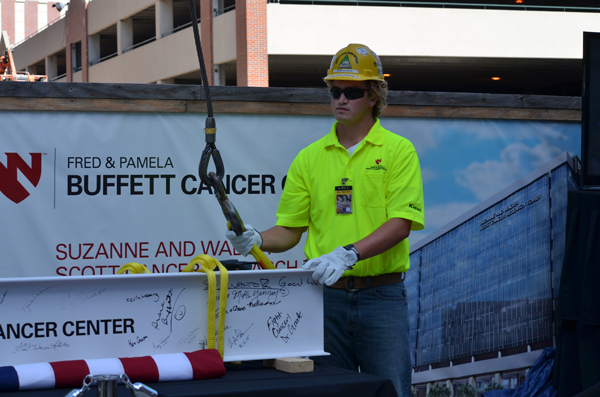 A construction worker helps raise a support beam into place during a ceremony at the Fred & Pamela Buffett Cancer Center. (Photo courtesy of UNMC)