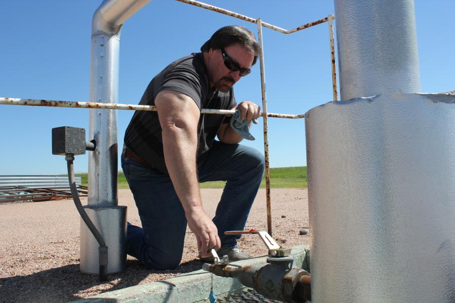 Field Inspector Mike Sutton checks an injection well. (Photo by Fred Knapp, NET News)