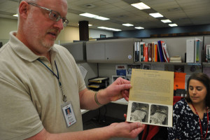 John Schleicher holds up an example of a stereoscopic card Erin Torell had found. (Photo by Ryan Robertson, KVNO News)