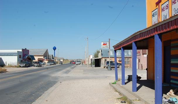 A street scene in Whiteclay, with man lying on sidewalk to right. (Photo by Fred Knapp, NET News)
