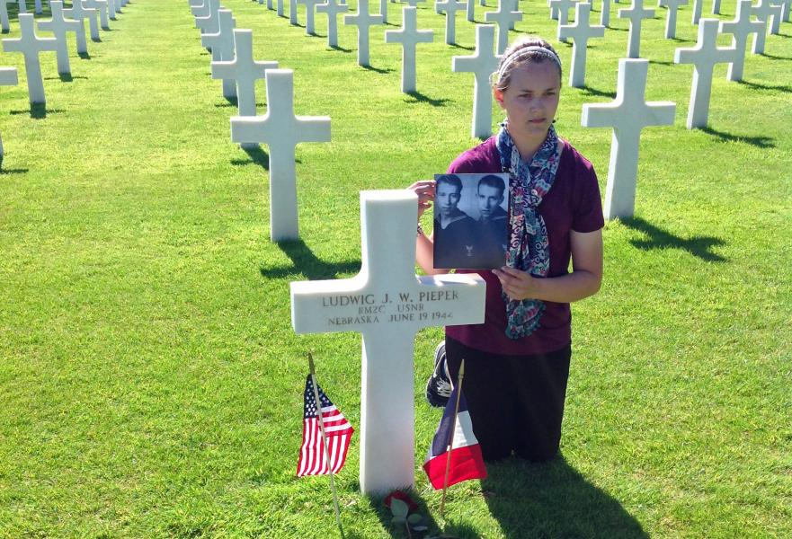 Vanessa Taylor at Normandy American Cemetery, holding a photo of the Pieper twins. (Photo courtesy Nichole Flynn)