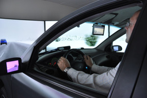 Screens take the place of rear view and side view mirrors in the driving simulator. (Photo by Ryan Robertson, KVNO News)