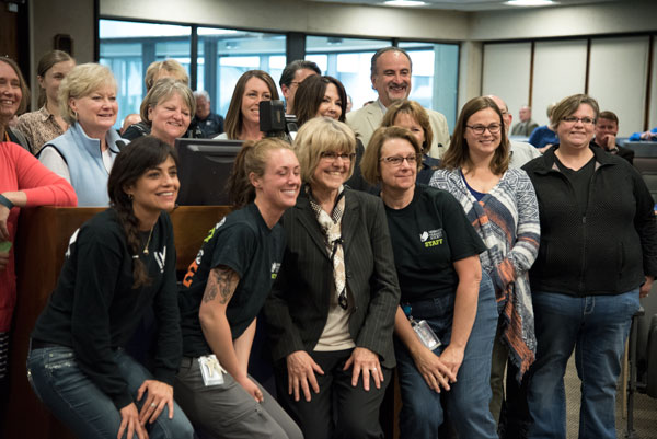 Judy Varner (front, center) stands with staff from Omaha Humane Society. Varner is retiring as the CEO of the Humane Society after 18 years. (Photo by Ryan Robertson, KVNO News)