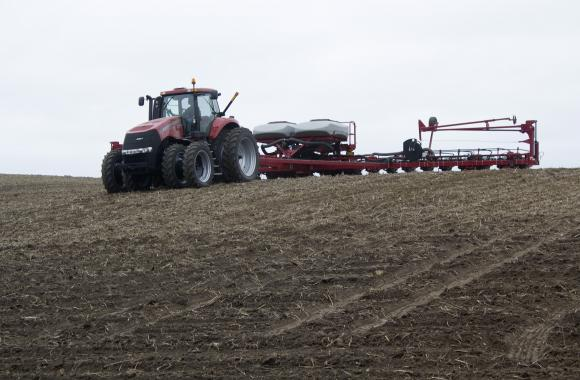 A farm hand on the Nelson farm in north Iowa drives a tractor pulling a 24-row planter as it drops corn seed into the field. (Amy Mayer/Harvest Public Media)
