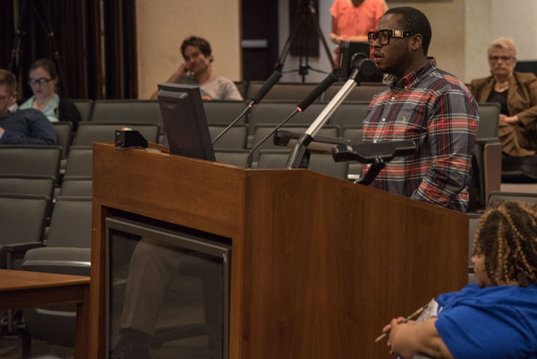 Octavius Johnson stands at the podium in the legistlative chambers. Johnson said he and his family were coerced into making a settlement agreement, and wants to take his case to trial. (Photo by Ryan Robertson, KVNO News)