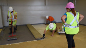 Tina Diaz-Ciehomski watches her Future Construction crew glue carpet at Omaha Public School's swing school on 60th street. (Photo by Ryan Robertson, KVNO News)