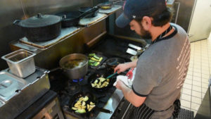 Colin Duggan of Kitchen Table prepares sliced vegetable to go with the Burmese style curry he's making for New American Dish. (Photo by Ryan Robertson, KVNO News)